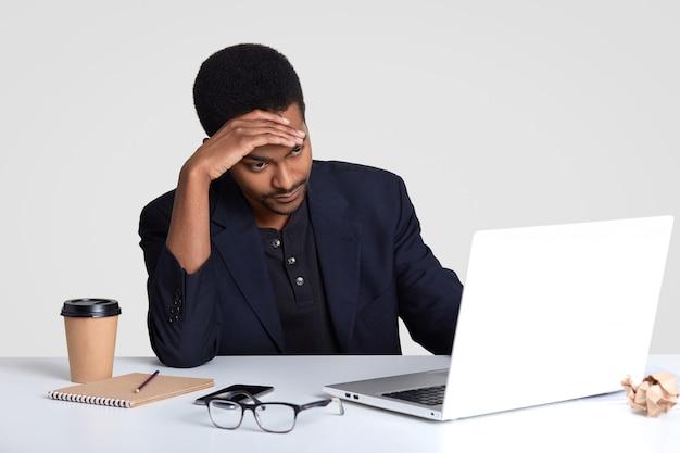 Fatigue fatiguée, l'homme non rasé à la peau sombre se sent travaillé après une longue période de travail, garde la main sur le front, ressent la migraine, porte un costume formel, utilise le bloc-notes pour écrire des enregistrements, boit du café à emporter