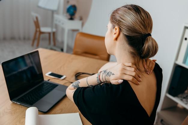Fatigué femme d'affaires surmené au lieu de travail dans le bureau, tenant son cou
