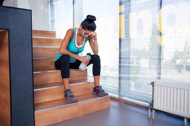Fatigué femme assise sur les escaliers avec une bouteille d'eau dans la salle de sport