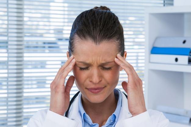 Fatigué femme médecin ayant des maux de tête