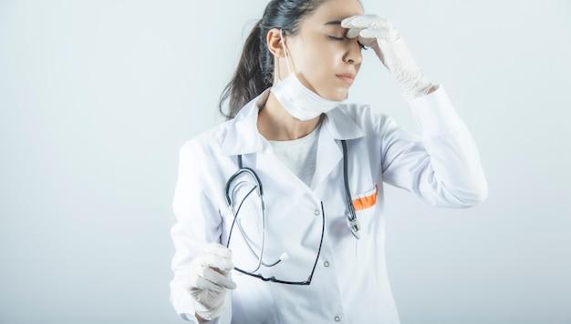 Fatigué femme médecin main dans le nez