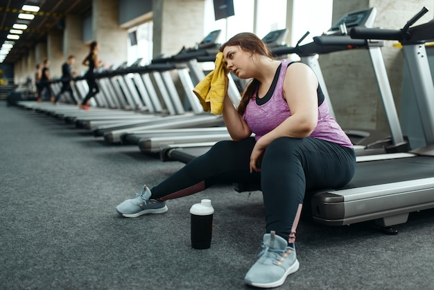 Fatigué femme en surpoids assis sur un tapis roulant dans une salle de sport, loisirs après une formation active. personne de sexe féminin obèse lutte contre l'excès de poids, entraînement aérobie contre l'obésité, club de sport