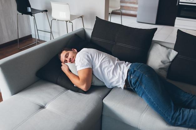 Fatigué gars épuisé allongé sur le canapé en position horizontale et rêvassant. profitez-en seul. dormez bien. moment paisible et paisible.