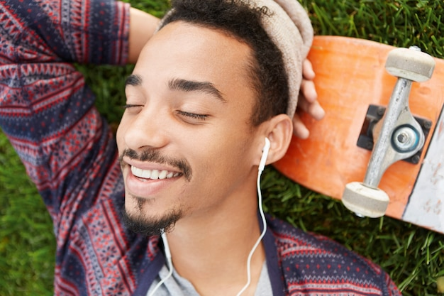 Fatigué et heureux, un jeune patineur talentueux fait la sieste sur une pelouse verte, sourit joyeusement en voyant des rêves agréables