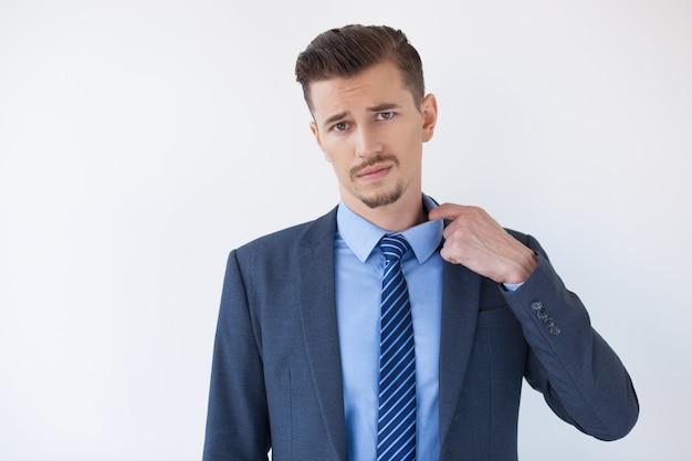 Fatigué homme d'affaires se sentir chaud et pulling collar