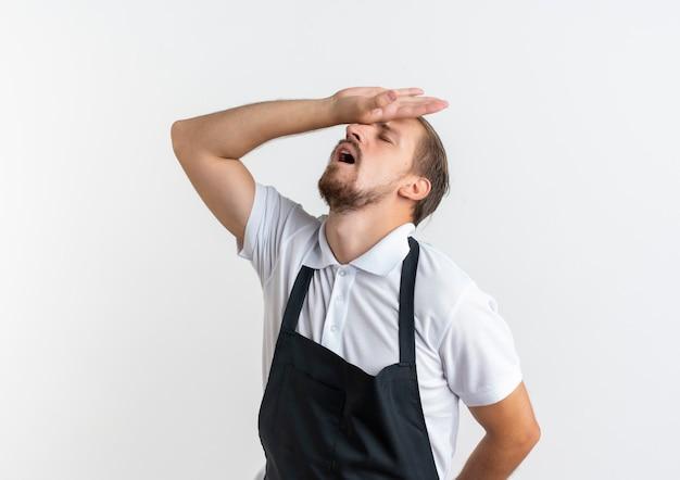Fatigué de jeune beau coiffeur en uniforme mettant la main sur le front avec les yeux fermés isolé sur un mur blanc