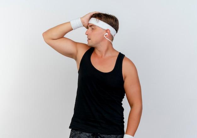 Fatigué de jeune bel homme sportif portant un bandeau et des bracelets avec un casque mettant la main sur la tête avec les yeux fermés isolé sur fond blanc avec espace copie
