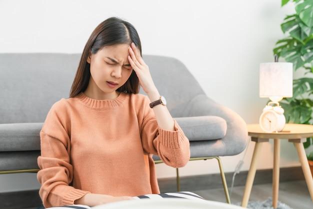 Fatigué de jeune femme asiatique ayant un mal de tête