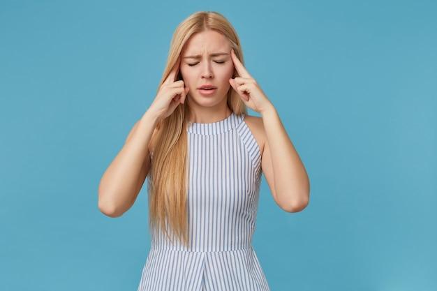 Fatigué de jeune femme blonde aux cheveux longs gardant l'index sur les tempes, fermant les yeux à cause de maux de tête, posant en robe d'été à rayures