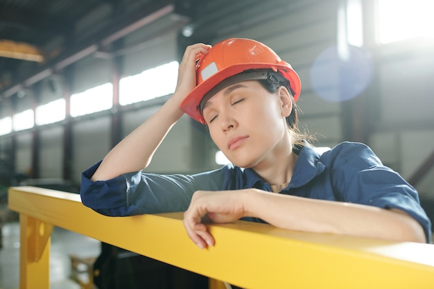 Fatigué de jeune femme ingénieur en vêtements de travail et sieste de casque tout en se penchant par un bar au milieu de la journée de travail