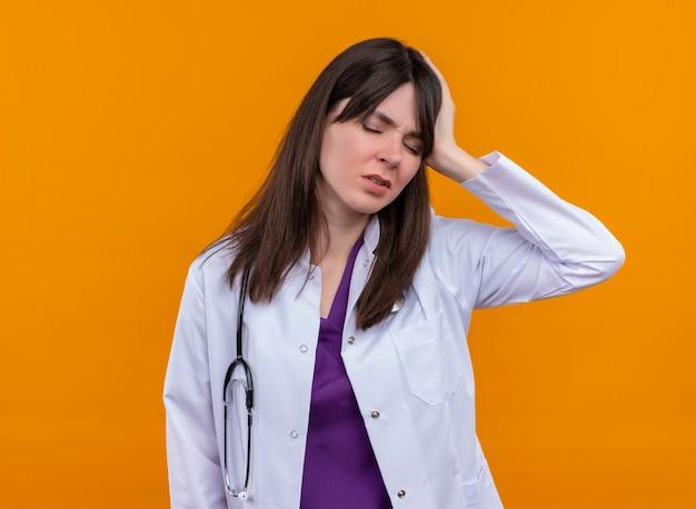 Fatigué de jeune femme médecin en robe médicale avec stéthoscope tient la tête avec la main sur fond orange isolé avec copie espace