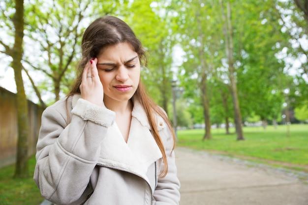 Fatigué de jeune femme touchant le temple dans le parc