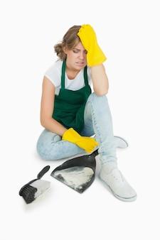 Fatigué jeune fille assise avec brosse et bac à poussière