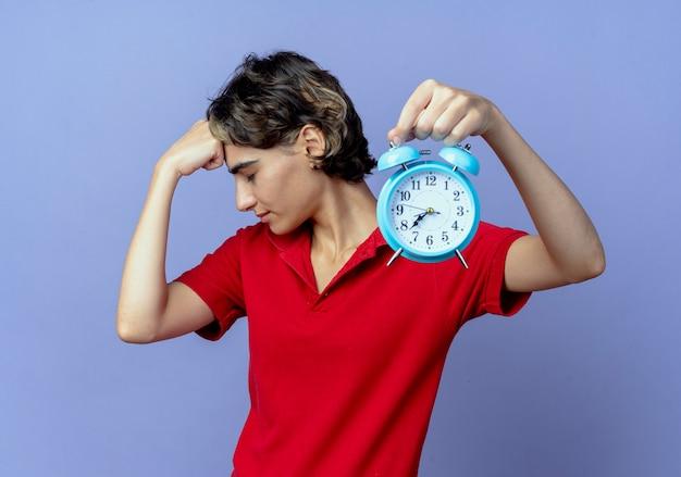Fatigué de jeune fille de race blanche avec coupe de cheveux de lutin qui s'étend de réveil à la caméra mettant le poing sur le front avec les yeux fermés isolé sur fond violet