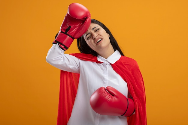 Fatigué de jeune fille de super-héros caucasien portant des gants de boîte touchant la tête avec les yeux fermés isolé sur fond orange avec espace de copie