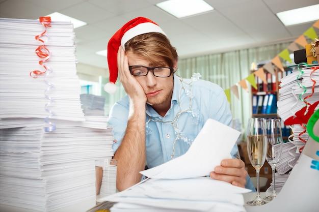 Fatigué de jeune homme d'affaires assis sur le lieu de travail parmi les papiers le jour de noël.