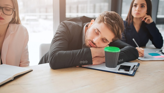 Fatigué de jeune homme assis à table et dormir dans la salle de réunion. il tient la tête sur les mains. des jeunes femmes s'assoient à côté de lui et écoutent. ils ont l'air concentrés.