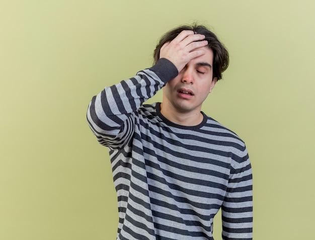 Fatigué jeune homme malade mettant la main sur le front isolé sur vert olive