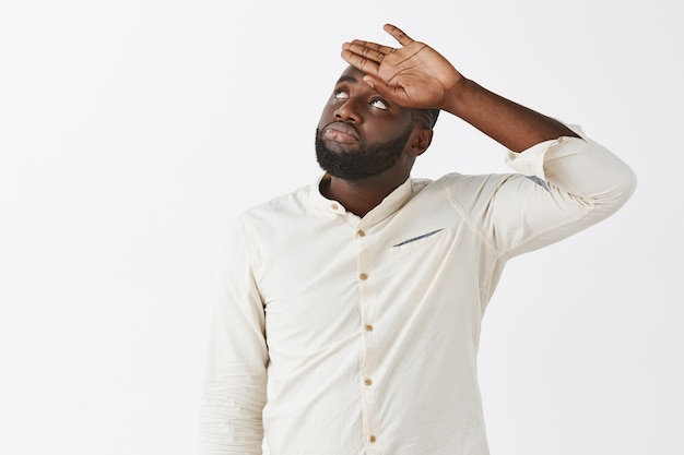 Fatigué de jeune homme posant contre le mur blanc