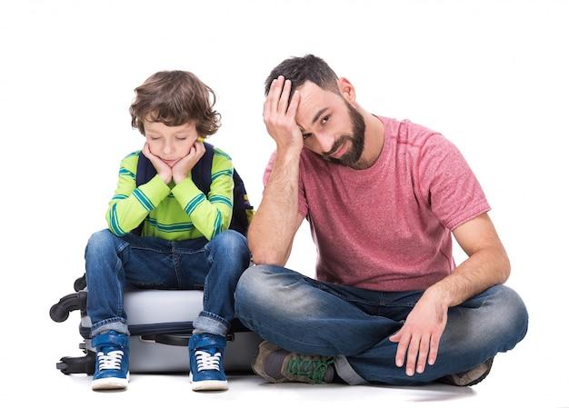 Fatigué jeune homme avec son fils est assis avec des bagages.