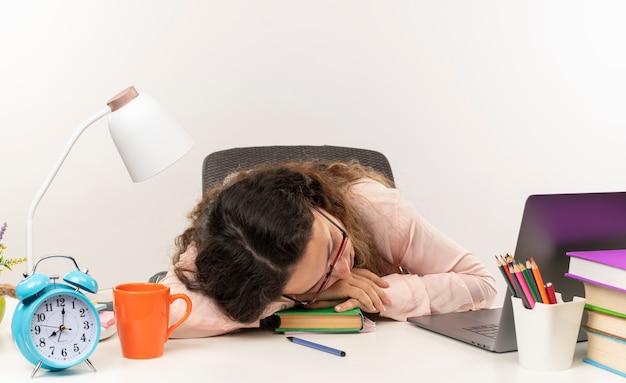 Fatigué de jeune jolie écolière portant des lunettes assis et dormir au bureau avec des outils scolaires isolé sur fond blanc