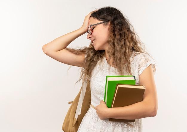 Fatigué de jeune jolie écolière portant des lunettes et sac à dos tenant des livres mettant la main sur la tête avec les yeux fermés isolé sur fond blanc