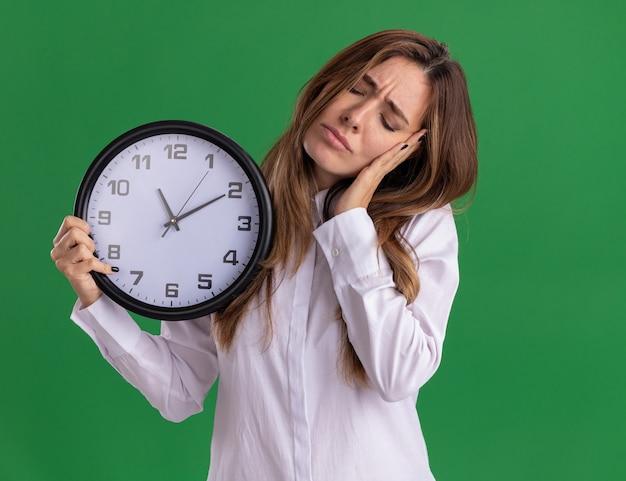 Fatigué de jeune jolie fille caucasienne met la main sur le visage et tient l'horloge sur le vert
