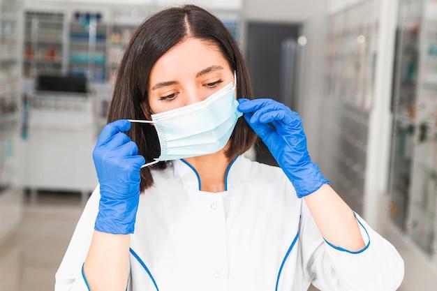Fatigué de jeune médecin ou pharmacien de l'ethnie du moyen-orient décollant un masque médical bleu et des gants dans le couloir de l'hôpital.