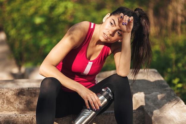 Fatigué de jeune sportive tenant une bouteille d'eau