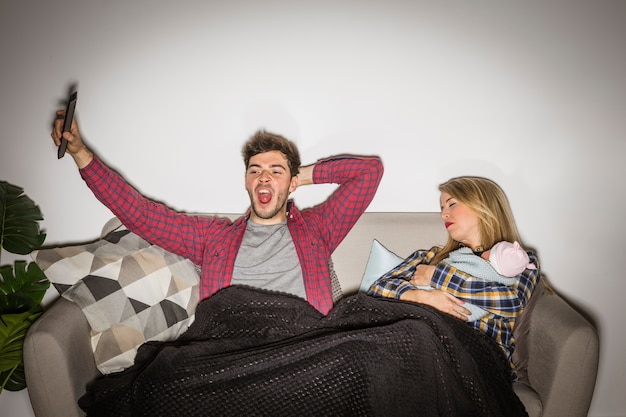 Fatigué père en regardant la télévision pendant que la mère avec bébé dort