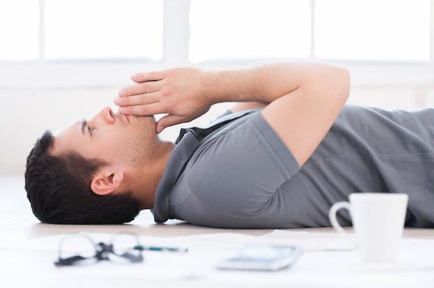 Fatigué et surmené. gentil jeune homme tenant les mains jointes en position couchée sur le sol avec des documents et une tasse de café dessus