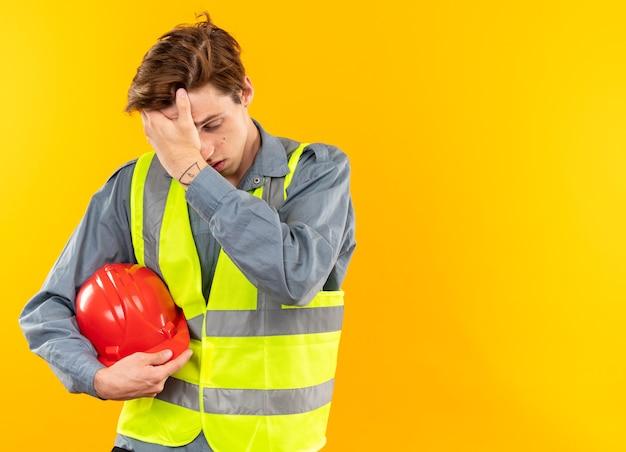 Fatigué de la tête baissée jeune homme constructeur en uniforme tenant un casque de sécurité mettant la main sur le front isolé sur un mur jaune