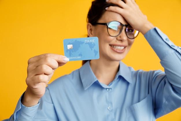 Fatigué de la vente. dame à lunettes tenant une carte de crédit et a mis sa main sur sa tête. pas d'argent sur la carte.