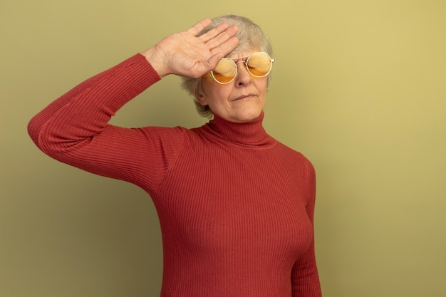 Fatigué de vieille femme portant un pull à col roulé rouge et des lunettes de soleil touchant la tête avec les yeux fermés