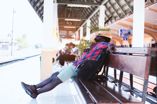 Fatigué voyageur africain dormant sur un banc à la gare