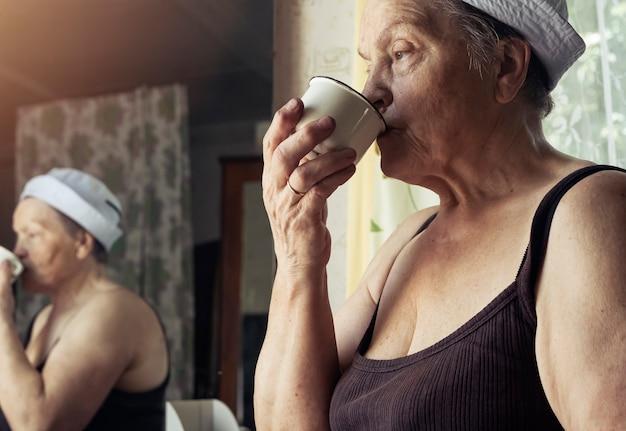 Fatigué d'une vraie agricultrice mature de l'eau potable de la tasse et à la triste portrait de femme candide