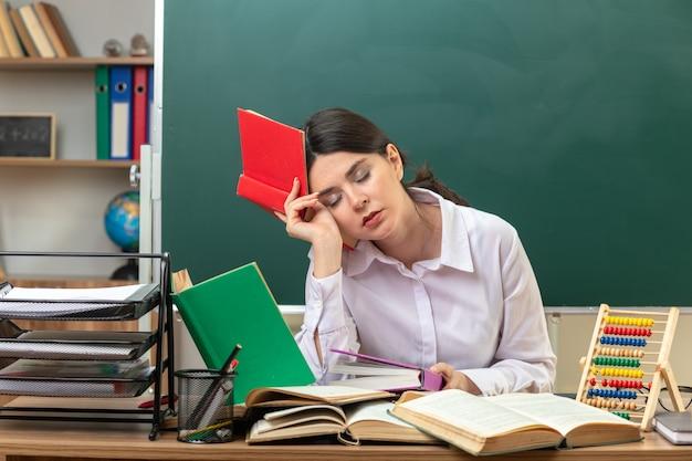 Fatigué avec les yeux fermés jeune enseignante tenant un livre autour de la tête assis à table avec des outils scolaires en classe