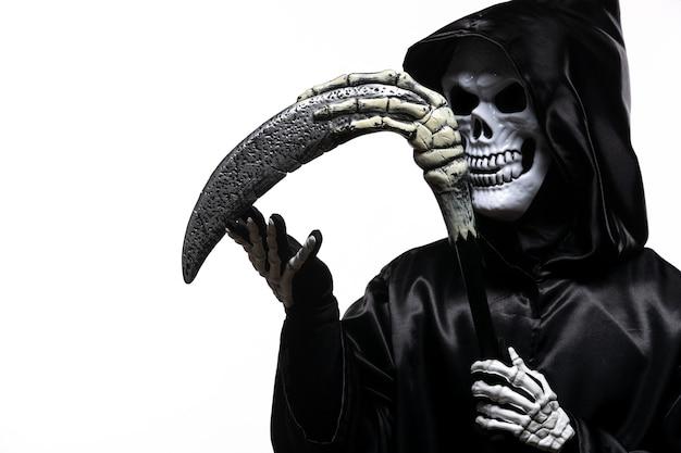 Faucheuse effrayante en vêtements noirs avec faux sur blanc