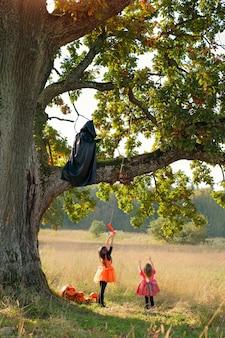 La faucheuse est assise sur un arbre et taquine les enfants avec un bonbon attaché à une canne à pêche