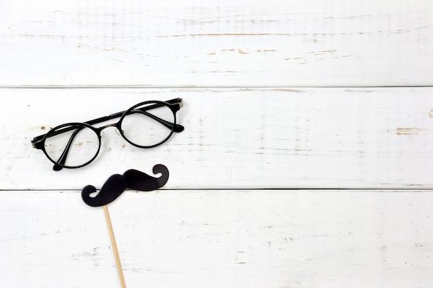 Fausse moustache sur fond blanc en bois en forme de cœur de papier. concept de fête des pères heureux.