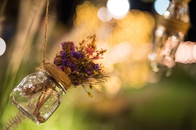 Fausses fleurs dans une bouteille en verre de soda suspendue dans un jardin avec un arrière-plan flou lumineux la nuit. décoration extérieure de mariage avec espace de copie pour le texte.