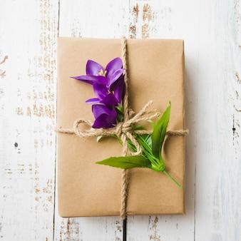 Fausses fleurs pourpres et coffret cadeau attachées avec une ficelle sur fond en bois