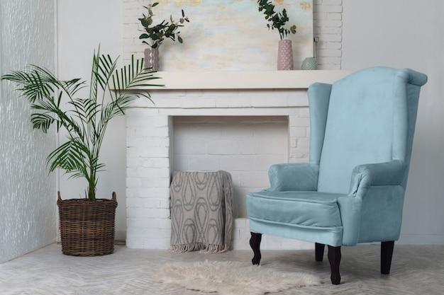 Fauteuil bleu et plantes d'intérieur avec cheminée. meubles de salon classiques et plantes en pot