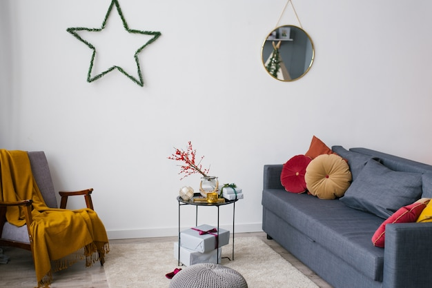 Fauteuil, canapé et table basse dans le salon, décorés pour noël et le nouvel an