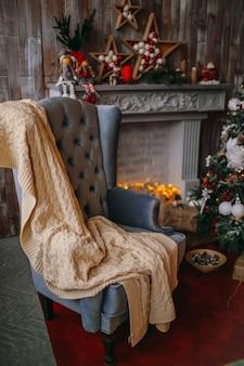 Fauteuil confortable avec couverture se tient devant un arbre de noël