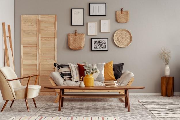 Fauteuil de couleur crème tendance à l'intérieur du salon scandinave avec galerie d'affiches sur mur beige