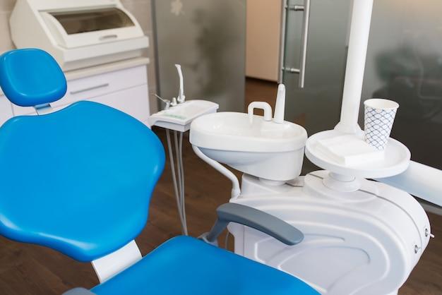 Fauteuil dentaire bleu dans une clinique dentaire blanche.