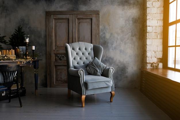 Fauteuil gris avec armoire sombre dans une chambre classique