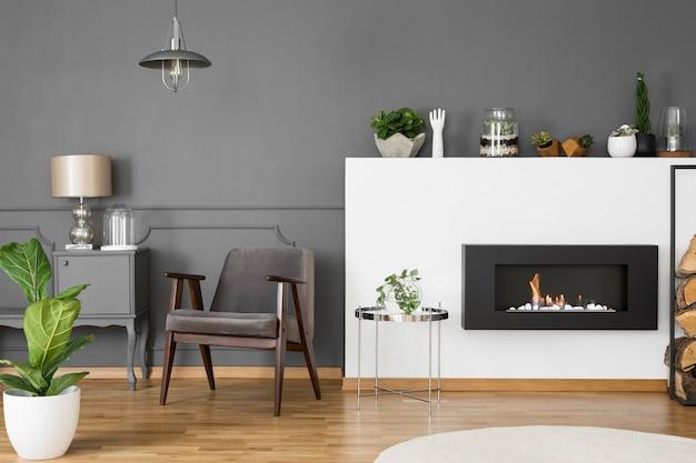 Fauteuil gris entre cheminée et meuble avec lampe en intérieur plat avec plante. vrai photo