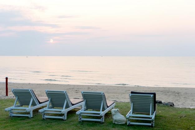 Fauteuil-lit sur la plage de sable, tôt le matin